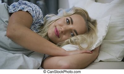 Pretty woman lying in bed in morning - Charming young woman...