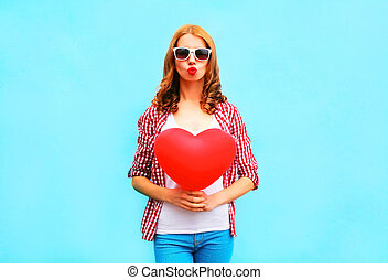 Pretty woman makes an air kiss with red balloon in the shape of heart on blue background