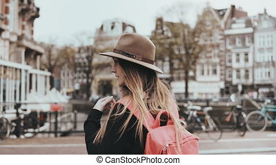 Pretty woman making a phone call. Back view 4K. Young female with long hair, red backpack in stylish hat on a bridge.