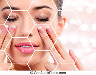 Pretty woman massaging her face, skin treatment concept. Abstract background with blurred lights