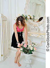 Pretty woman near the mirror in the bedroom with a bouquet of roses