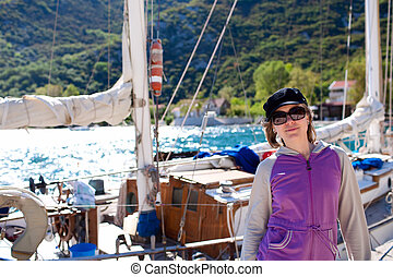 Pretty woman near the wooden yacht