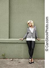 Pretty woman next to wall