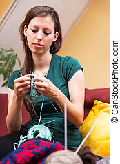 woman on a couch is knitting