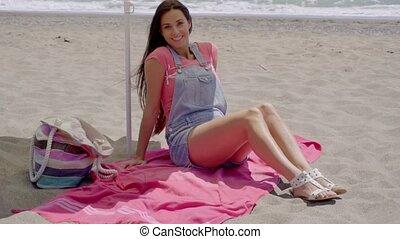 Pretty woman on blanket in shade on beach - Pretty smiling...