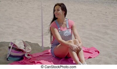 Pretty woman on blanket under beach umbrella