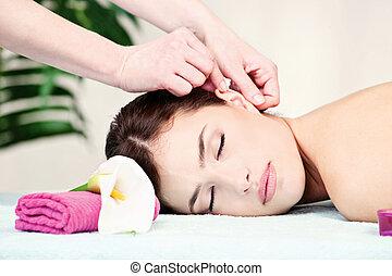 woman on ear massage in salon
