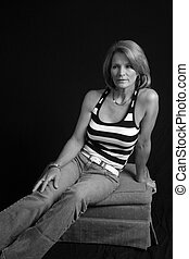 A pretty, mature, woman is sitting on a hassock in black and white.