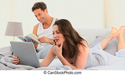 Pretty woman  on her laptop while her husband is reading
