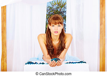 woman on massage table under canopy