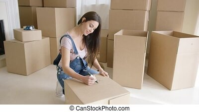 Attractive woman packing up her personal belongings as she prepares to move house kneeling down writing the contents of a box on the lid
