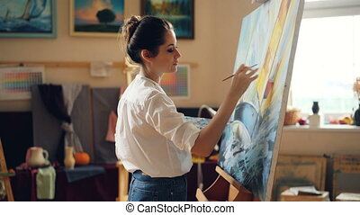 Pretty woman painter is depicting seascape then looking at...