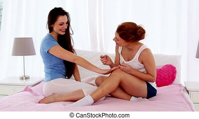 Pretty woman painting her friends nails