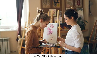 Pretty woman painting teacher is teaching young girl to mix paints on palette creating beautiful color during art class in nice modern studio. People and education concept.