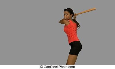 Pretty woman playing baseball on gr