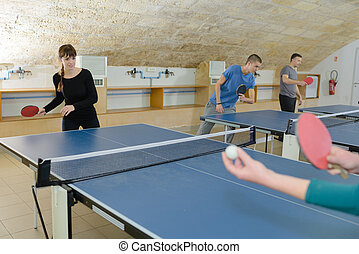 pretty woman playing ping-pong with friends