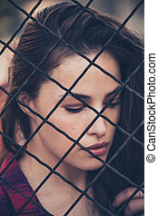 pretty woman portrait behind fence shot in the city