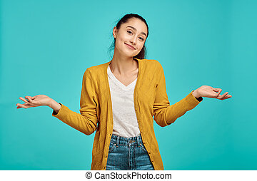 Pretty woman portrait, blue background, positive emotion. Face expression, female person looking on camera in studio, emotional concept, feelings