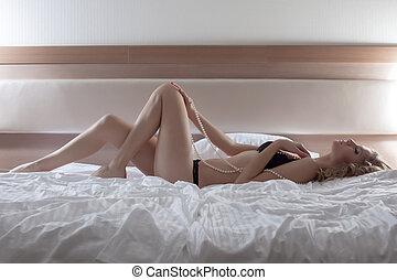 Pretty woman posing in black lingerie on huge bed