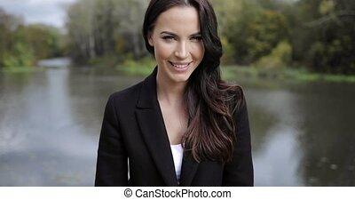 Pretty woman posing near river