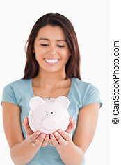 Pretty woman posing with a piggy bank