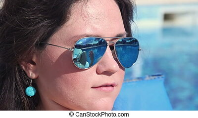 Pretty woman puts sunscreen oil on body, sunglasses reflection