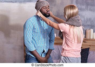 Pretty woman putting hat on her boyfriend