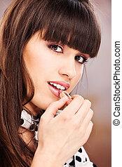 Pretty woman putting lipstick