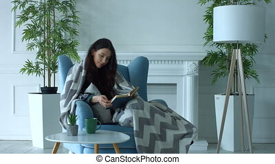 Pretty woman reading a book in armchair at home