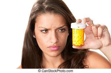 Pretty woman reading the label on a prescription bottle