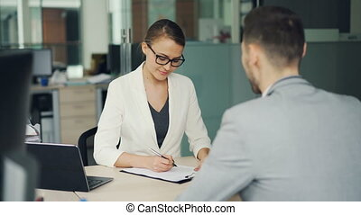 Pretty woman recruiter is talking to male candidate during job interviewer in office, girl is taking notes then shaking his hand and laughing. Success and workplace concept.