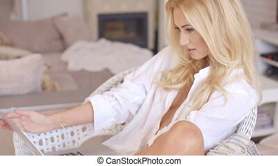 Pretty woman relaxing in a wicker chair - Pretty sexy blond...