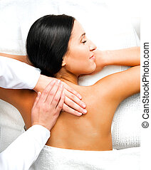 Pretty woman relaxing while getting a back massage