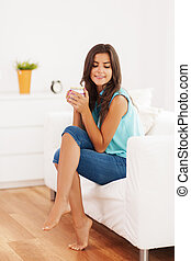 Pretty woman relaxing with cup of coffee at home