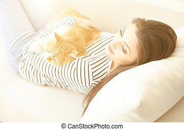 Pretty woman resting with animal at home