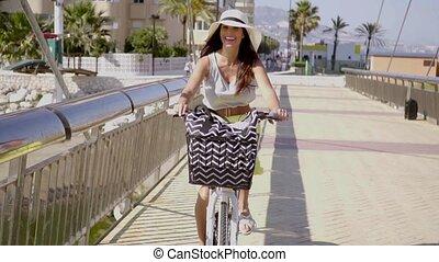 Pretty woman riding along a seafront promenade