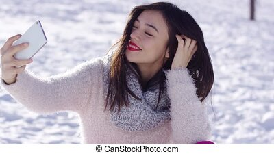 Pretty woman sat on snow taking selfie