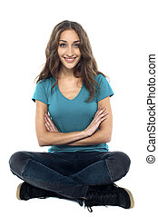 Pretty woman seated on the floor with hands crossed