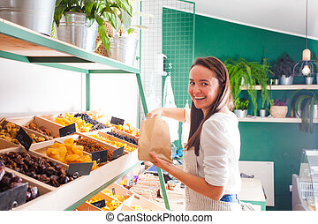 Pretty woman seller in the grocery shop