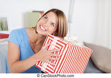 Pretty woman shaking a large present