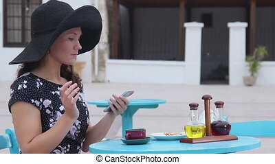 """""""Pretty woman sitting at street cafe, typing message on smartphone, smiling"""""""