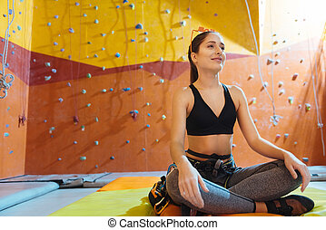 Pretty woman sitting in a lotus posture in climbing gym