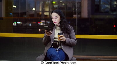 Pretty woman sitting on a bus station, drinking coffee with smartphone, having night city at the background.