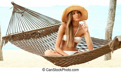 Pretty woman sitting on hammock at the tropical beach