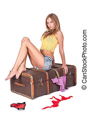 Pretty woman sitting on old suitcase