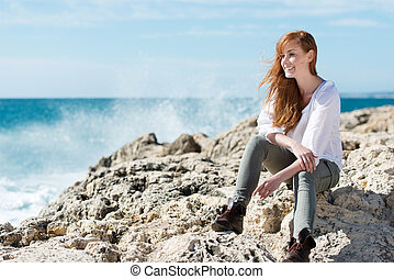 Pretty woman sitting on rocks
