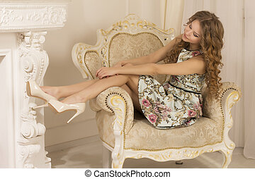 Pretty woman sitting on the armchair
