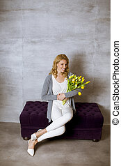 Pretty woman sitting on the sofa with a bouquet of yellow tulips