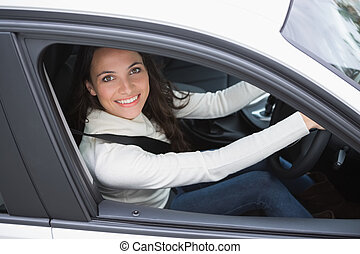 Pretty woman smiling and driving