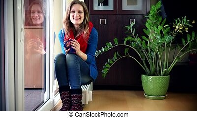 pretty woman smiling at camera sitting on radiator and drinking hot tea.